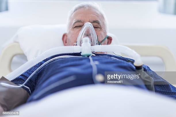 Senior patient in hospital with oxgen mask