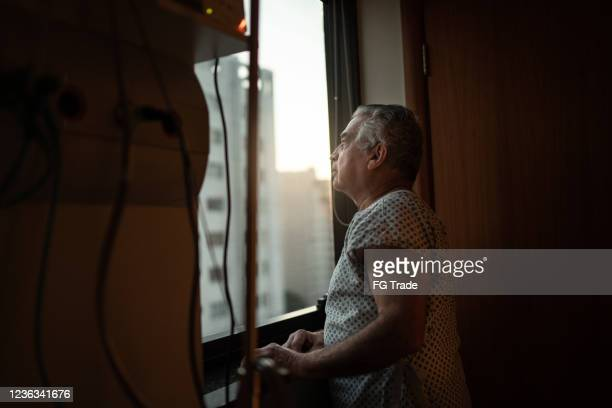 senior patient looking through window at hospital - cancer illness stock pictures, royalty-free photos & images