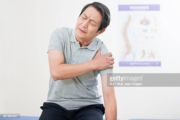 Senior patient rubbing his painful shoulder