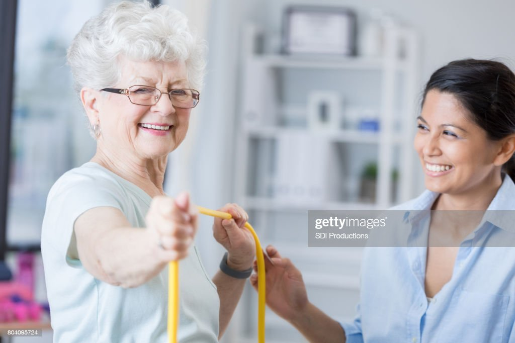 Senior patient smiles with therapist while using exercise band : Stock Photo