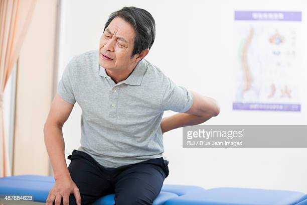 senior patient suffering from backache - bones stock photos and pictures