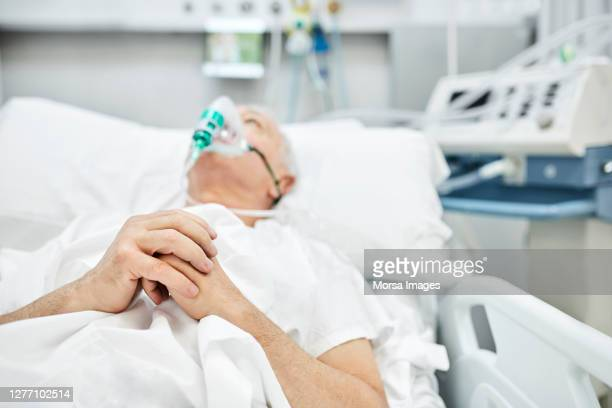 senior patient suffering from coronavirus praying on stretcher - oxygen mask stock pictures, royalty-free photos & images