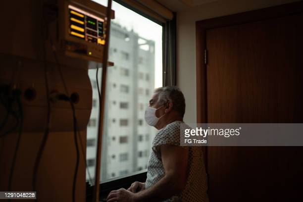 senior patient using mask looking through window at hospital - condition stock pictures, royalty-free photos & images
