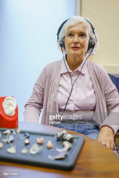 senior patient wearing headphones during hearing test while sitting at clinic - eine seniorin allein stock-fotos und bilder
