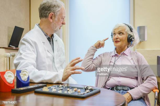 Senior patient wearing headphones talking to Audiologist during ear exam at doctors office
