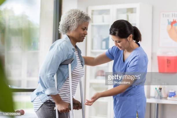 松葉杖とシニアの患者は若い看護婦さんに助けられ - 杖 ストックフォトと画像