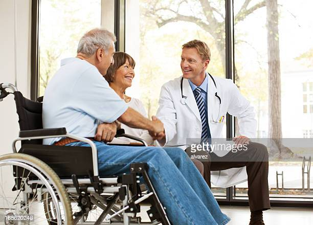 Senior patient with wife and doctor doing handshake