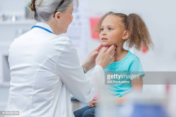 Senior pediatra examina niña