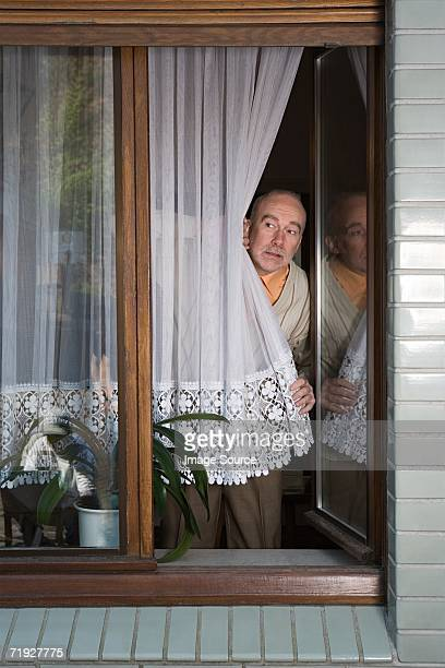 Senior peering around net curtain