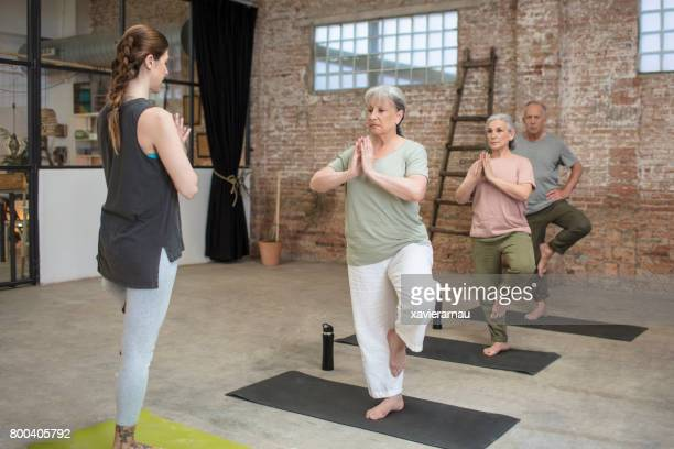 senior people and coach exercising in tree pose - standing on one leg stock pictures, royalty-free photos & images