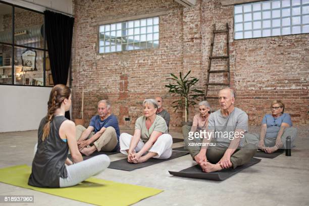Senior people and trainer exercising in class