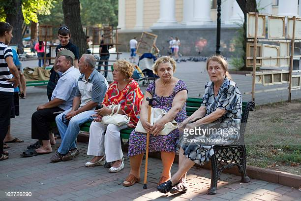 Senior people are enjoying socialising while sitting in a bench in teh one of Odessa's city's park. Ukraine, August 2012