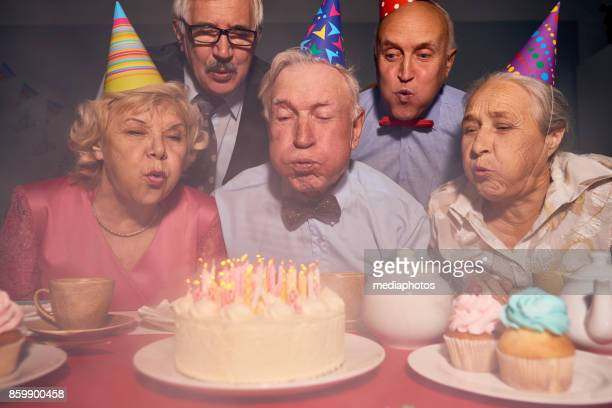 senior people at birthday party of friend - birthday candles stock photos and pictures
