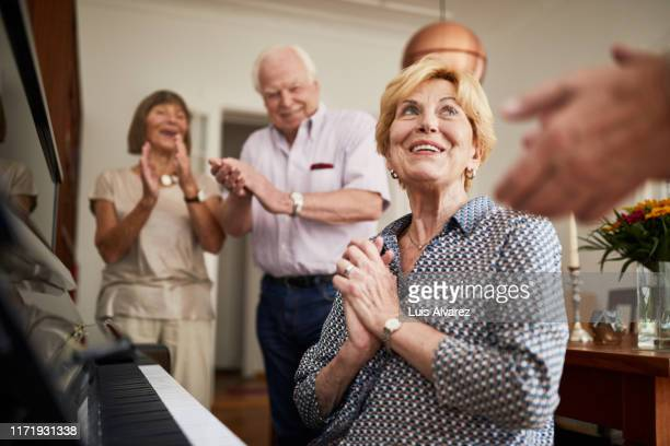 senior people clapping hands for a friend playing piano - incidental people stock pictures, royalty-free photos & images