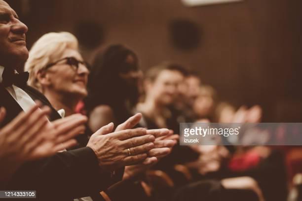personas mayores aplaudiendo en el teatro, concéntrate en las manos - gala fotografías e imágenes de stock