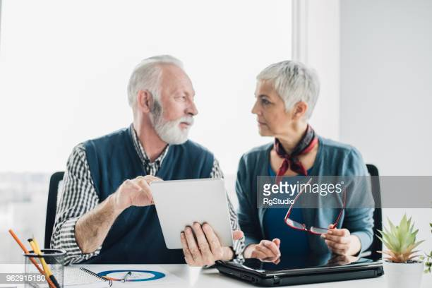 Senior people discussing paperwork at office