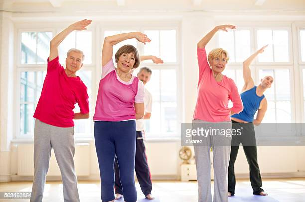 Senior gente haciendo estiramientos junto al gimnasio