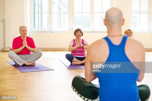 Senior people doing yoga at health club