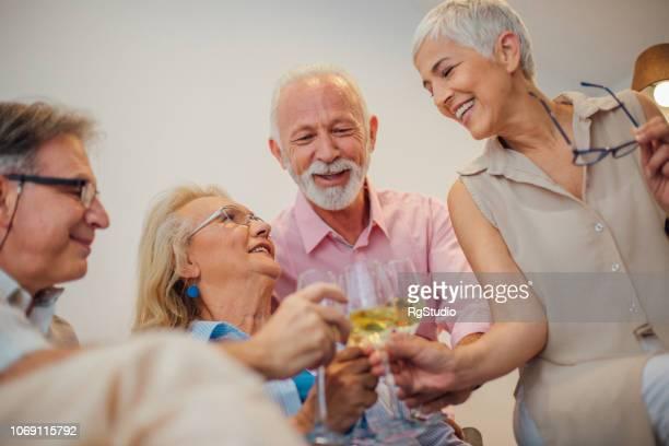 Senior people drinking white wine