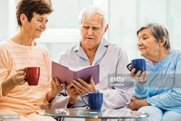 Senior pessoas a desfrutar ao ler um livro.