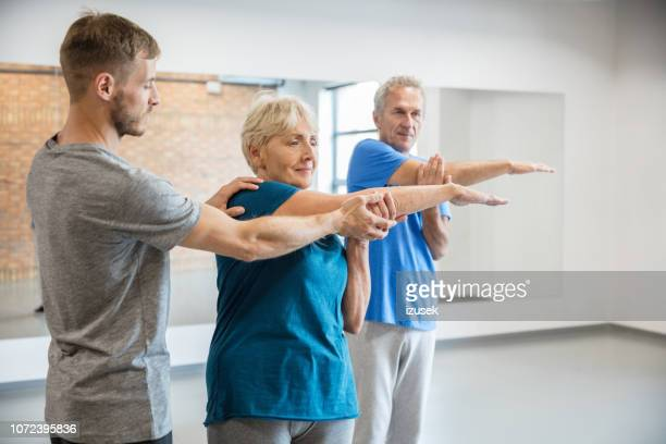 senior people exercising with trainer at rehab club - drug rehab stock pictures, royalty-free photos & images