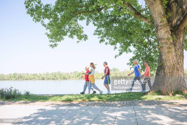 senior people, friends having sports activity outdoors - walking stock pictures, royalty-free photos & images