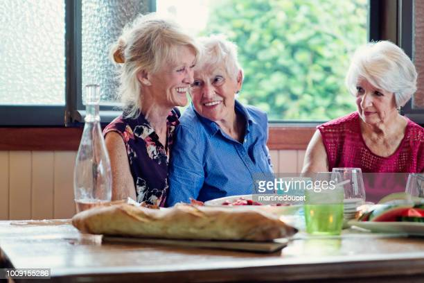 """senior people having dinner and conversation in summer house. - """"martine doucet"""" or martinedoucet stock pictures, royalty-free photos & images"""
