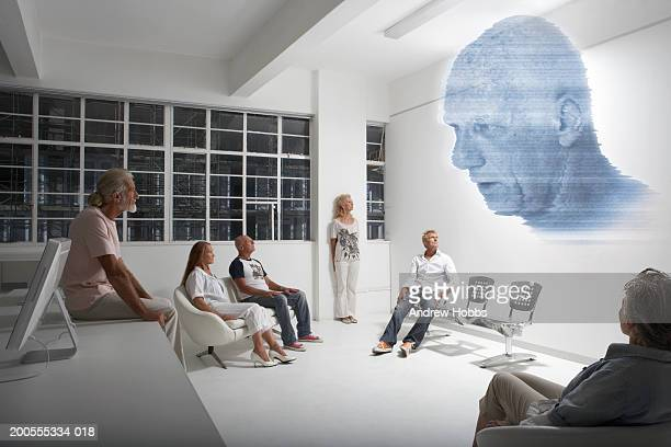 Senior people looking at face projected on wall (digital composite)