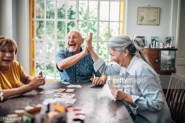 senior people playing cards in nursing home - active seniors stock pictures, royalty-free photos & images
