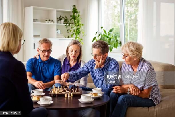 hogere mensen die schaak in pensioneringshuis spelen - izusek stockfoto's en -beelden