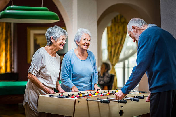senior people playing foosball at nursing home - care home stock pictures, royalty-free photos & images