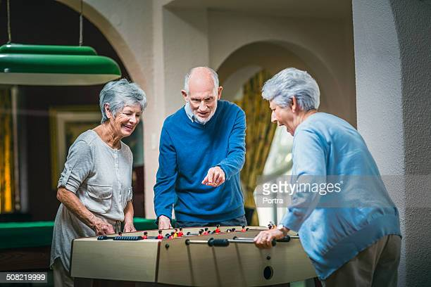senior people playing foosball at nursing home - retirement community stock pictures, royalty-free photos & images