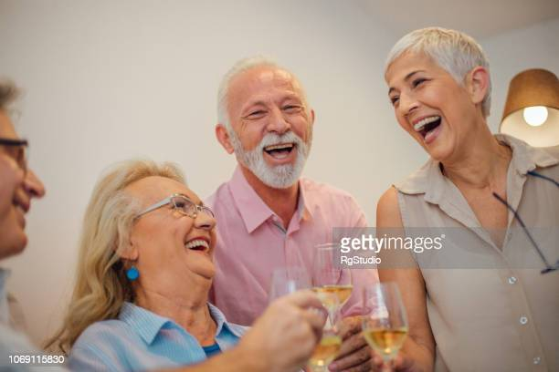 Senior people sharing a laugh over a glass of wine
