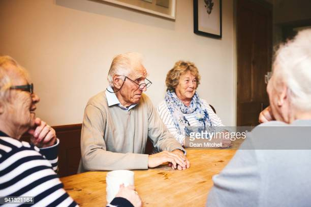 Senior people sitting at table in retirement home