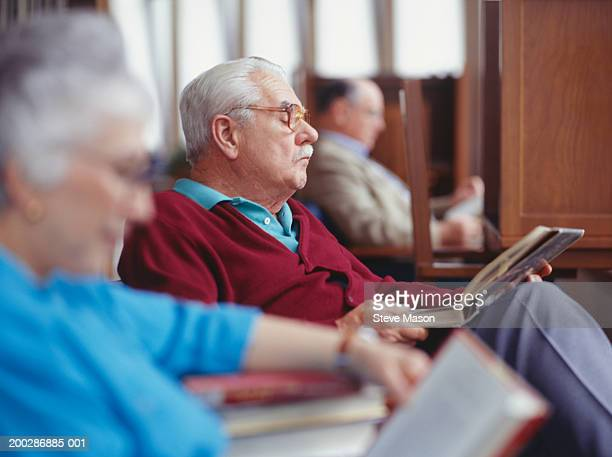 Senior people sitting in library, reading books, side view