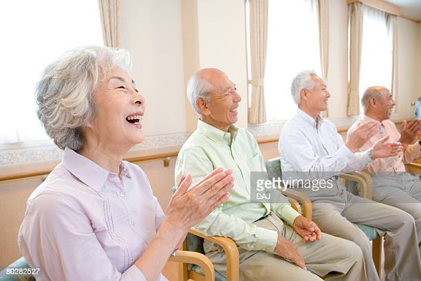 Senior people smiling and clapping hands in hospital