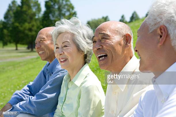 Senior people smiling and sitting on lawn, side by side