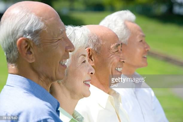 Senior people smiling in the field, side by side