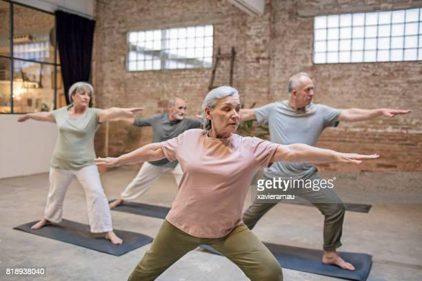 Senior people standing in warrior pose at gym