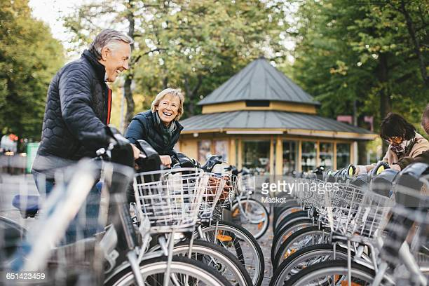 senior people taking rental bikes at parking lot - bicycle parking station stock photos and pictures
