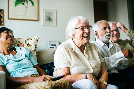 Senior people watching television together 1043564886
