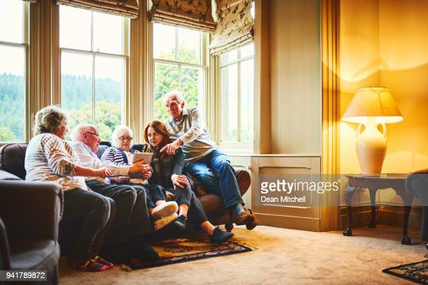 senior people with young woman using digital tablet at care home - hospice stock pictures, royalty-free photos & images