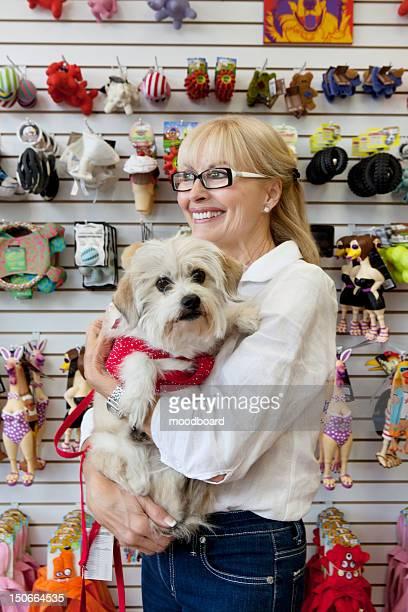 Senior pet shop owner standing with dog