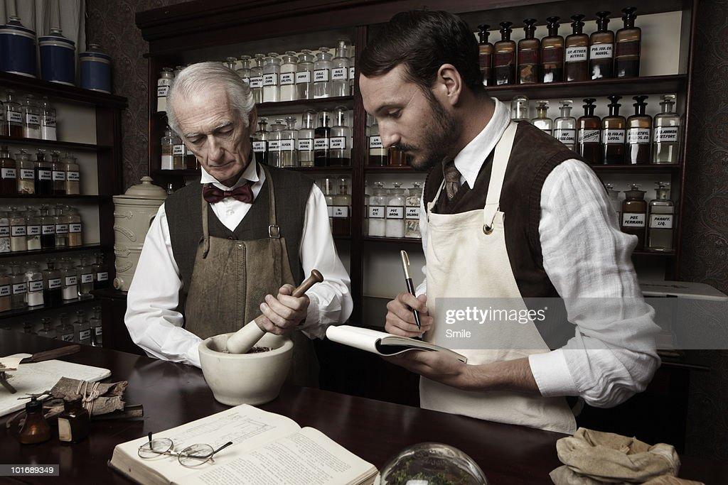 Senior pharmacist teaching his apprentice : Stock Photo