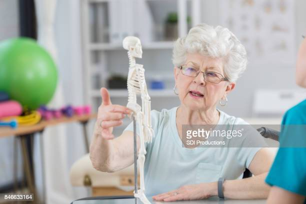 Senior physical therapy patient asks therapist questions about treatment