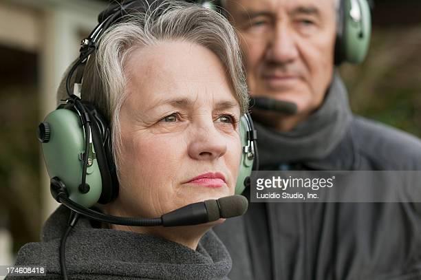 Senior pilot couple wearing aviation headsets