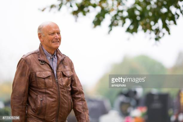 Senior Porträt - 73 Jahre alter Mann in Leder Jacke walking im Freien im Herbst