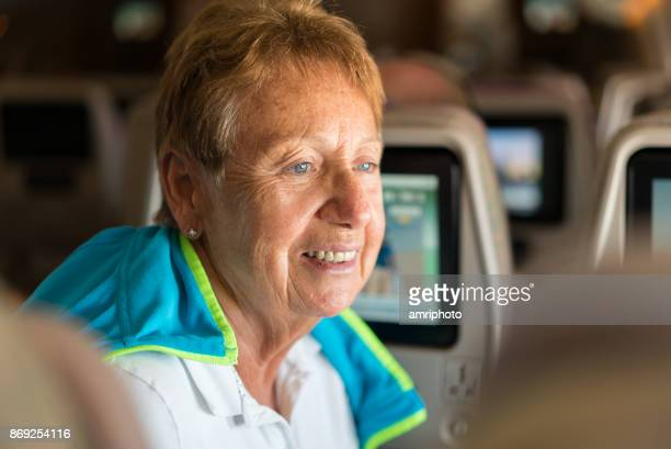 Senior portret - lachende 70 jaar oude vrouw in vliegtuig