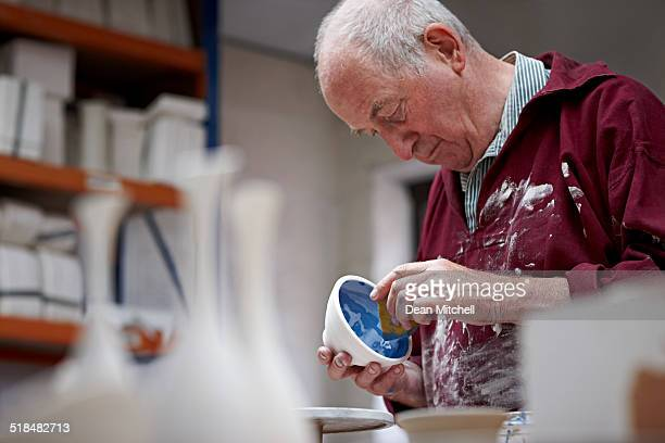 Senior potter painting a clay pot at workshop