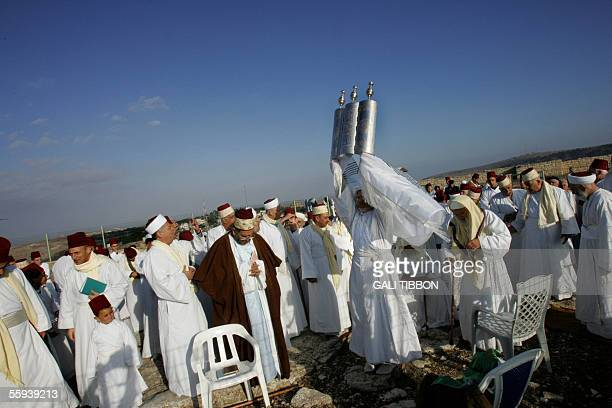 A senior priest of the tiny ancient Samaritan community wrapped in a prayer shawl holds a Tora scroll during the pilgrimage for The Holy day of...
